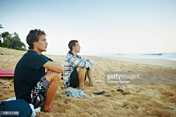 Two brothers sitting on beach watching surf