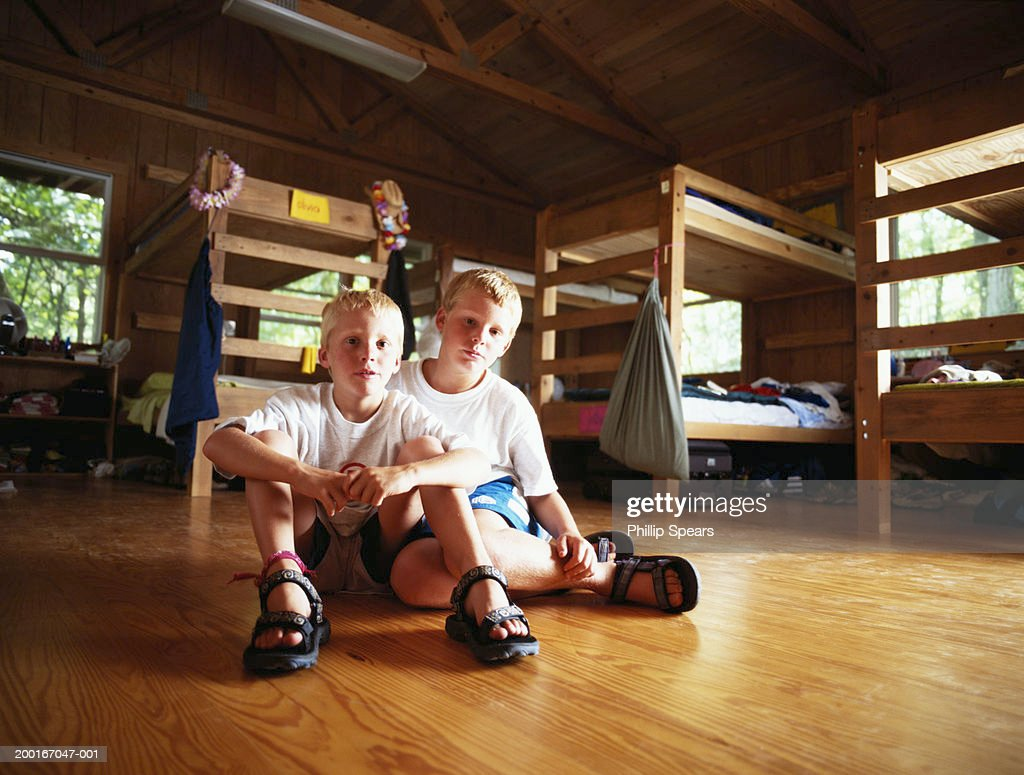 Two brothers (8-10) sitting on floor in cabin, bunkbeds in background : Stock Photo