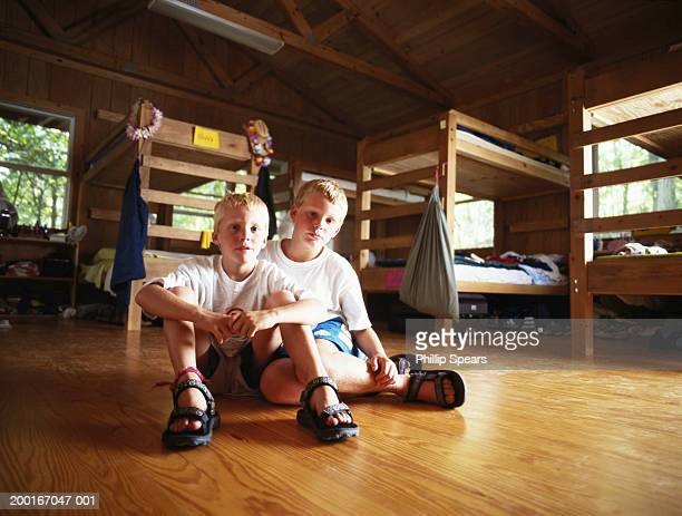Two brothers (8-10) sitting on floor in cabin, bunkbeds in background