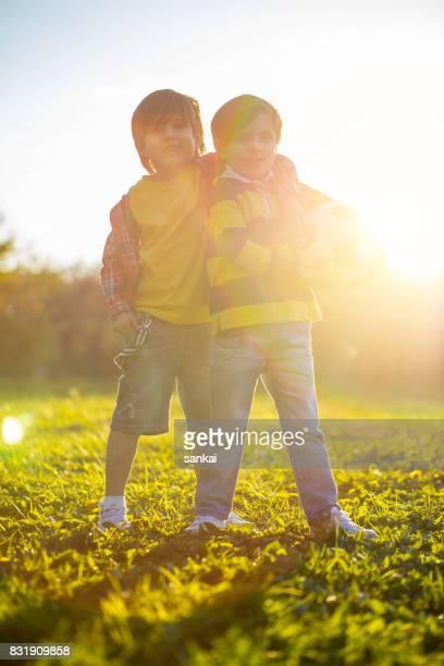 Zwei Brüder stehen zusammen mit Fußball im öffentlichen Park bei Sonnenuntergang