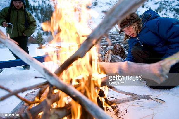 Two brothers start a campfire in the backcountry of California.