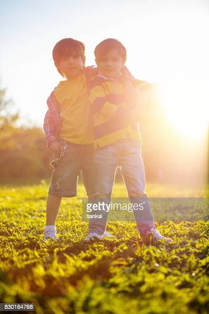Two brothers with soccer ball at public park at sunset