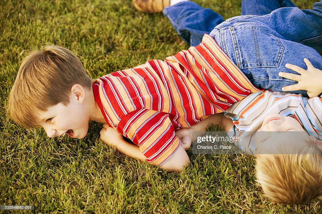 Two brothers (4-7) wrestling on lawn, laughing : Stock Photo