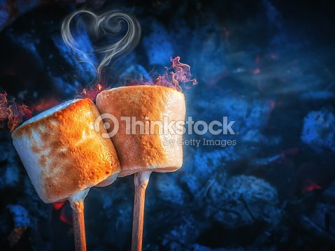 two brown sweet marshmallows roasting over fire flames smoke in form