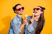 Two brunette hair lady isolated on yellow vivid background in glasses spectacles make beaming white toothy smile eating sugar tasty appetiser snack