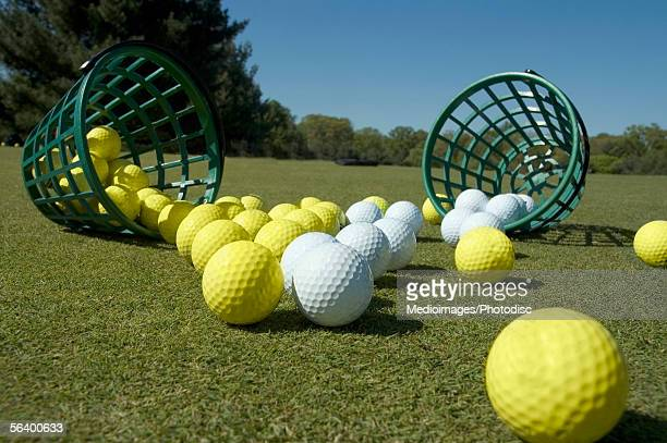Two buckets of balls tipped over on grass