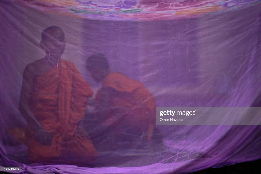 Two buddhist monks prepare their bed under a mosquito net at the Wat Kos Sokharar pagoda on December 8, 2013 near Phnom Penh, Cambodia. Marking the 65th International Human Rights Day, approximately 500 monks from Cambodia are marching in protest from December 1st to the 10th as they head to Phnom Penh to take part in coordinated anti-government protests. Joining them are communities, associations, networks, federations, unions and NGOs, as well as residents of the communities along the six designated routes.