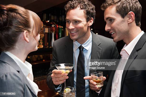 Two buisnessmen chatting to female colleague at bar