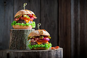 Two burger with onion, tomato and lettuce, chips and bacon