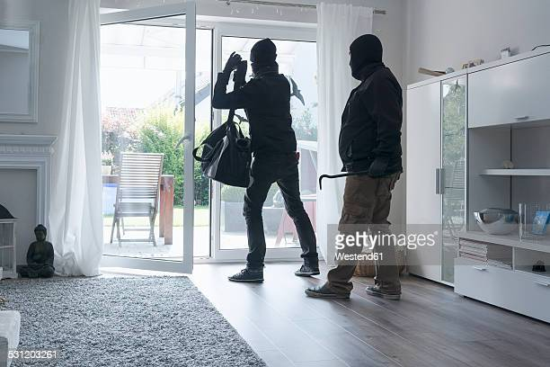 Two burglars leaving an one-family house with their loot at daytime