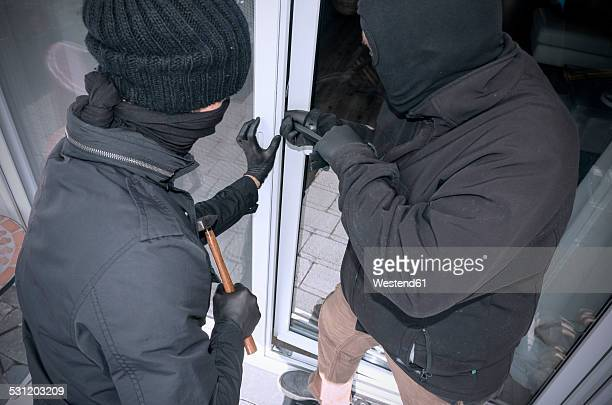 Two burglars opening terrace door of an one-family house with hammer and crowbar at daytime, partial view