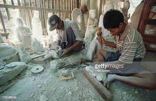 Two Burmese artisans chisel out marble sculptures of Buddha in different sizes and forms in a simple workshop on the outskirts of Mandalay