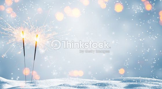 two burning sparklers in snow : Stock Photo