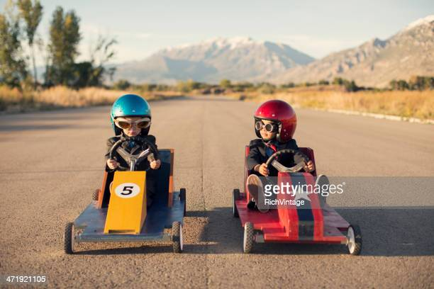 Two Business Boys Sit in Toy Cars on Street