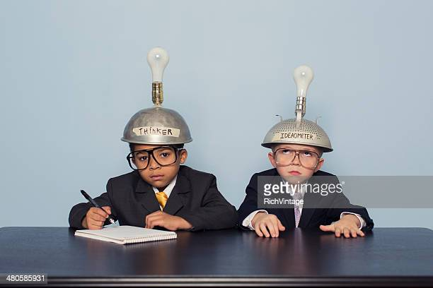 Two Business Boys Wearing Thinking Caps are Confused
