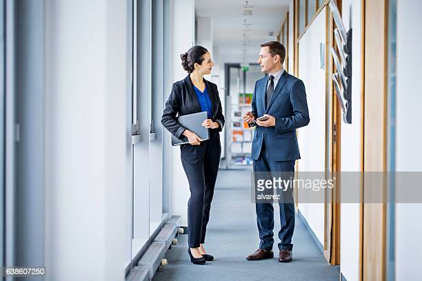 Two business colleagues discussing work in office