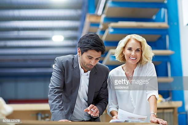 Two business colleagues doing paperwork in factory