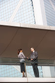 Two Business Colleagues Shaking Hands Outside Office Building