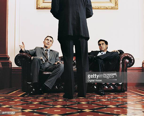 Two Business Colleagues Sitting on a Leather Sofa Being Greeted by Their CEO