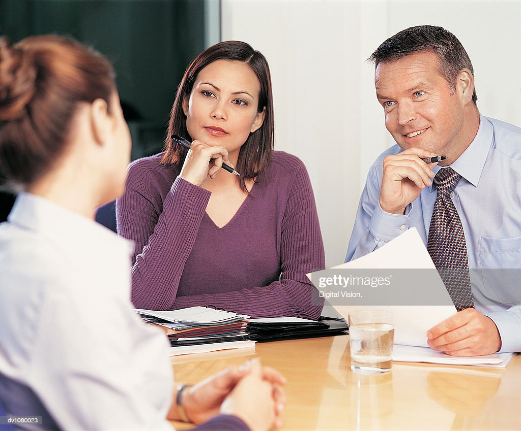Two Business Colleagues With an Application Form Conducting an Interview at a Table