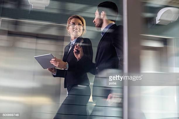 Dos compañeros de trabajo de negocios caminando por un pasillo elevado