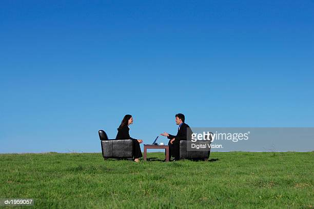 Two Business Executives Sitting in Armchairs on the Grass Talking to One Another