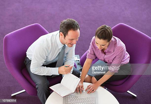 Two business executives working on laptop in modern office cafeteria