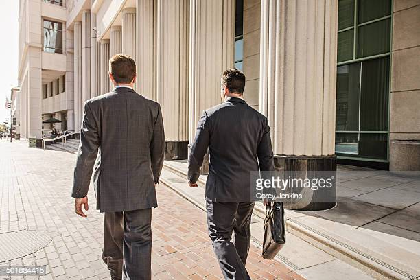 Two business lawyers with briefcase outside courthouse