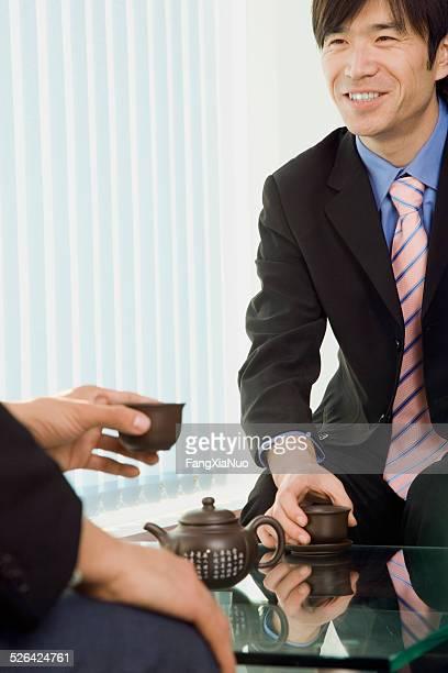 Two business men drinking tea