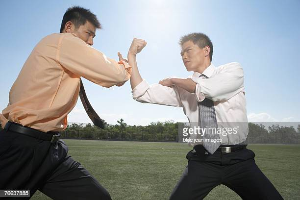 Two business men fighting with martial arts.