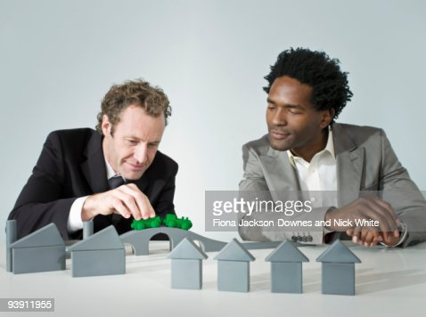 Two business men play with a train : Stock Photo