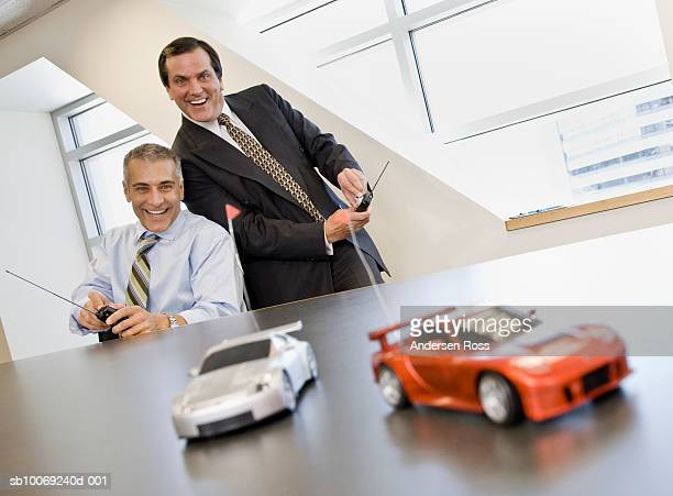 Two business men playing with remote control cars