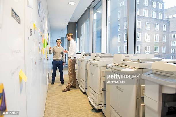 Two business men talking by notes on a wall and  printers.
