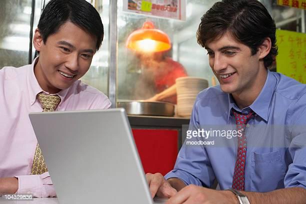 Two business men using laptop in bar