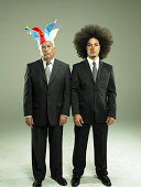 Two business men wearing clown hat and nose, portrait