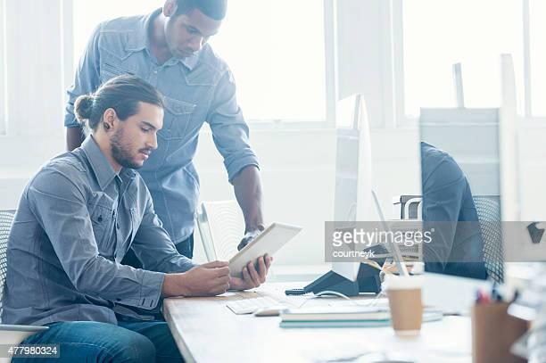 Two Business men working on digital tablet.