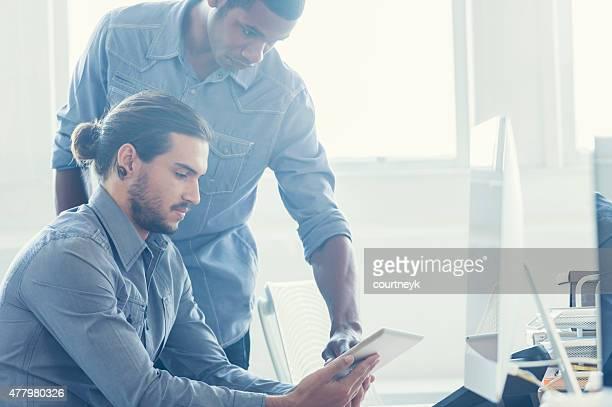 Due uomini d'affari, lavorando sulla tavoletta digitale.