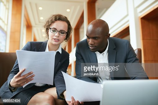 Two business partners sitting in cafe and discussing contract. : Stock Photo