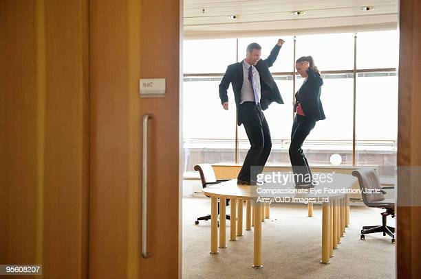 two business people dancing on boardroom table