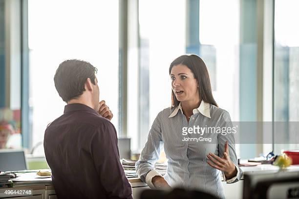 Deux hommes d'affaires ayant des discussions sérieuses dans bureau moderne
