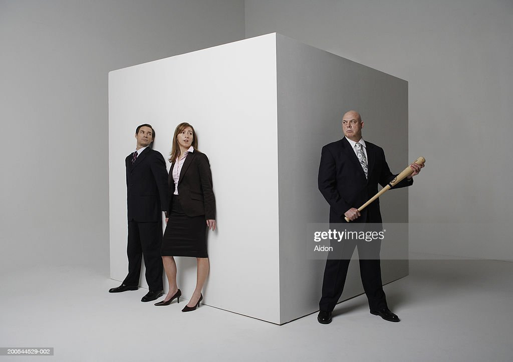 Two business people hiding from colleague with baseball bat : Stock Photo