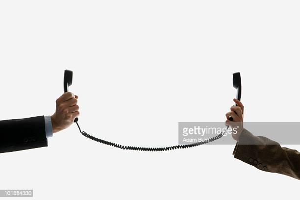 Two business people holding telephone receivers connect with the same cord