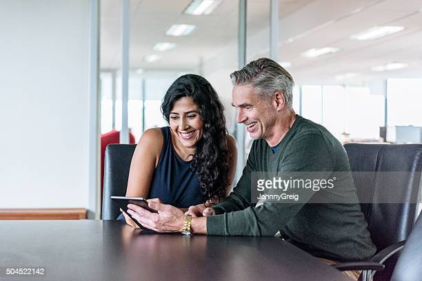 Two business people in office with digital tablet, smiling