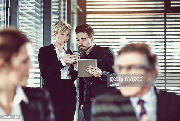 Two Business People Looking at Portable Devices