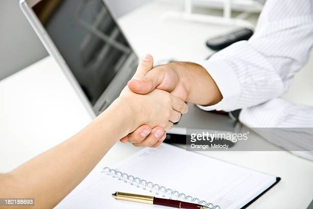 Two business people shake hands over laptop