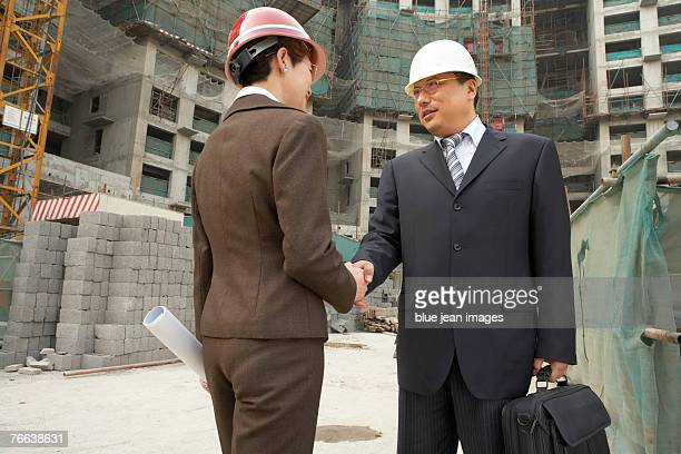 Two business people shaking hands at a construction site.