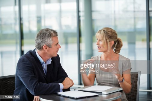 Two business people sitting, having a conversation