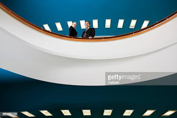 Two business people standing on a balcony