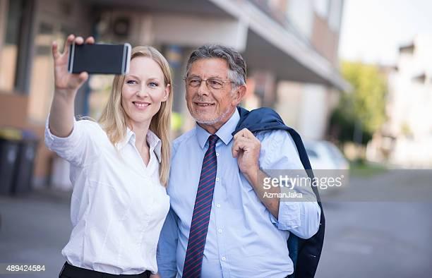 Deux hommes d'affaires prenant un selfie avec un Smartphone