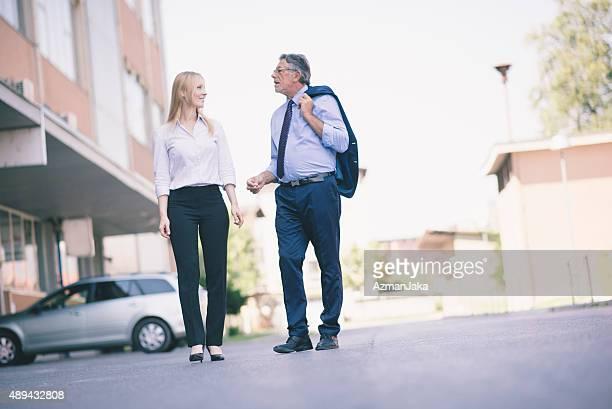 Duas pessoas de negócios, tendo um passeio e a falar